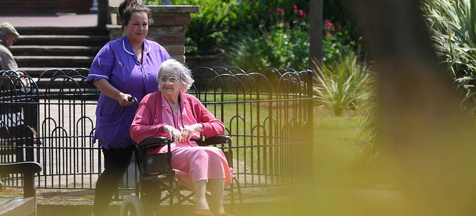 Chrislyn House care home resident in wheelchair with nurse.